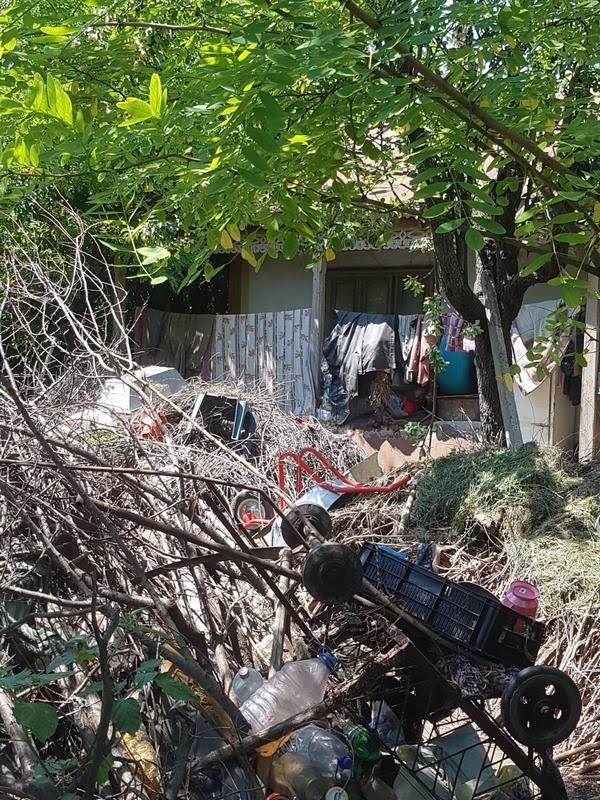 Îngropaţi în mizerie, de bunăvoie: O familie şi-a transformat curtea casei în groapă de gunoi